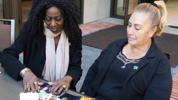 """Vertice Boyce (left) looks at family photos with Eva Maldonado (right), the mother of her donor, Berto Maldonado. The recipient of a kidney transplant in 2015, Berto Maldonado died in a car accident in July 2017, and his family re-donated, or """"re-gifted"""" his organ. The re-transplantation, an extremely rare procedure, was made possible by transplant surgeon Dr. Jeffrey Veale at Ronald Reagan UCLA Medical Center. His family says Berto would have wanted to give someone else the same second chance at life he received."""